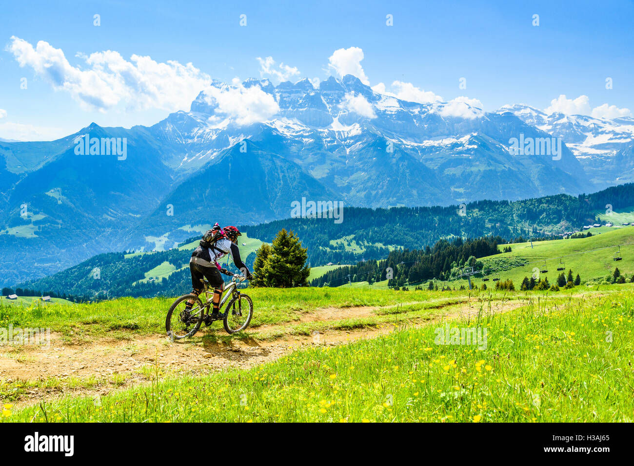 Rider participating in Pass'Portes du Soleil MTB 2016, with view of the Dents du Midi - Stock Image