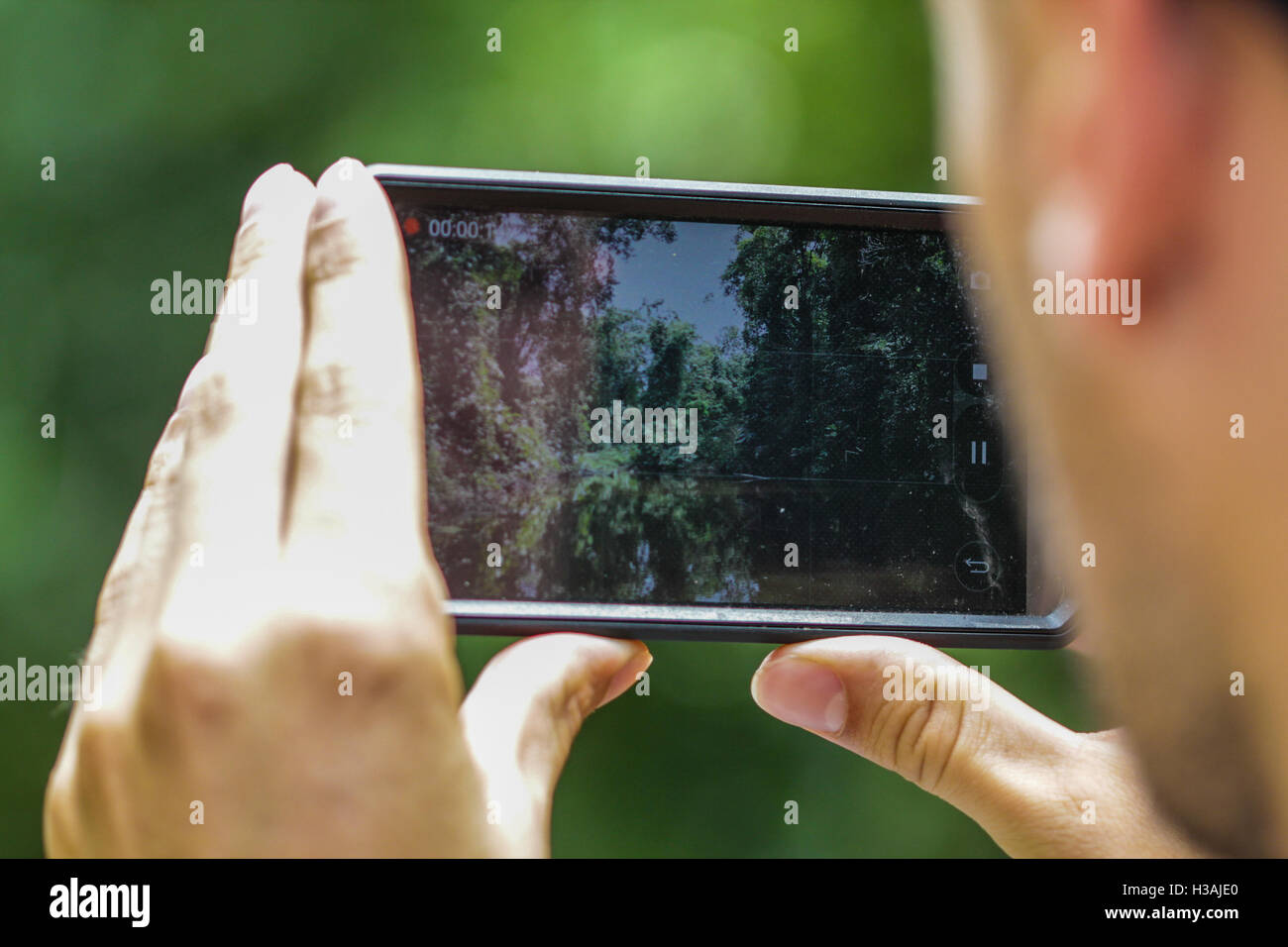 Young tourist is using his smartphone to capture and image and find his location in the mountains - Stock Image