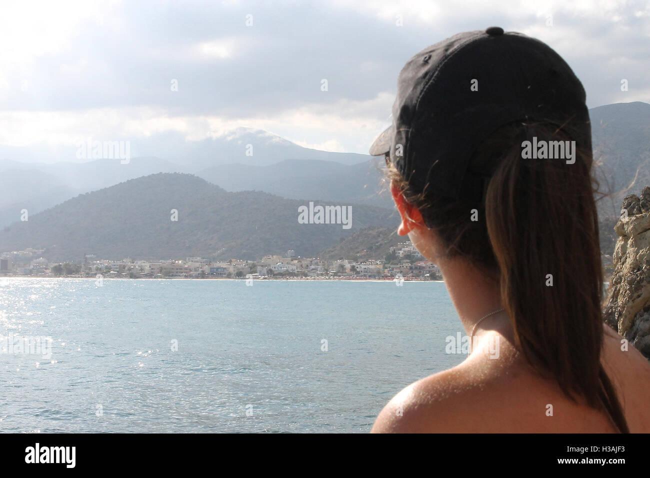 A lady looks out onto Stalis Stalida Crete Greece Stock Photo