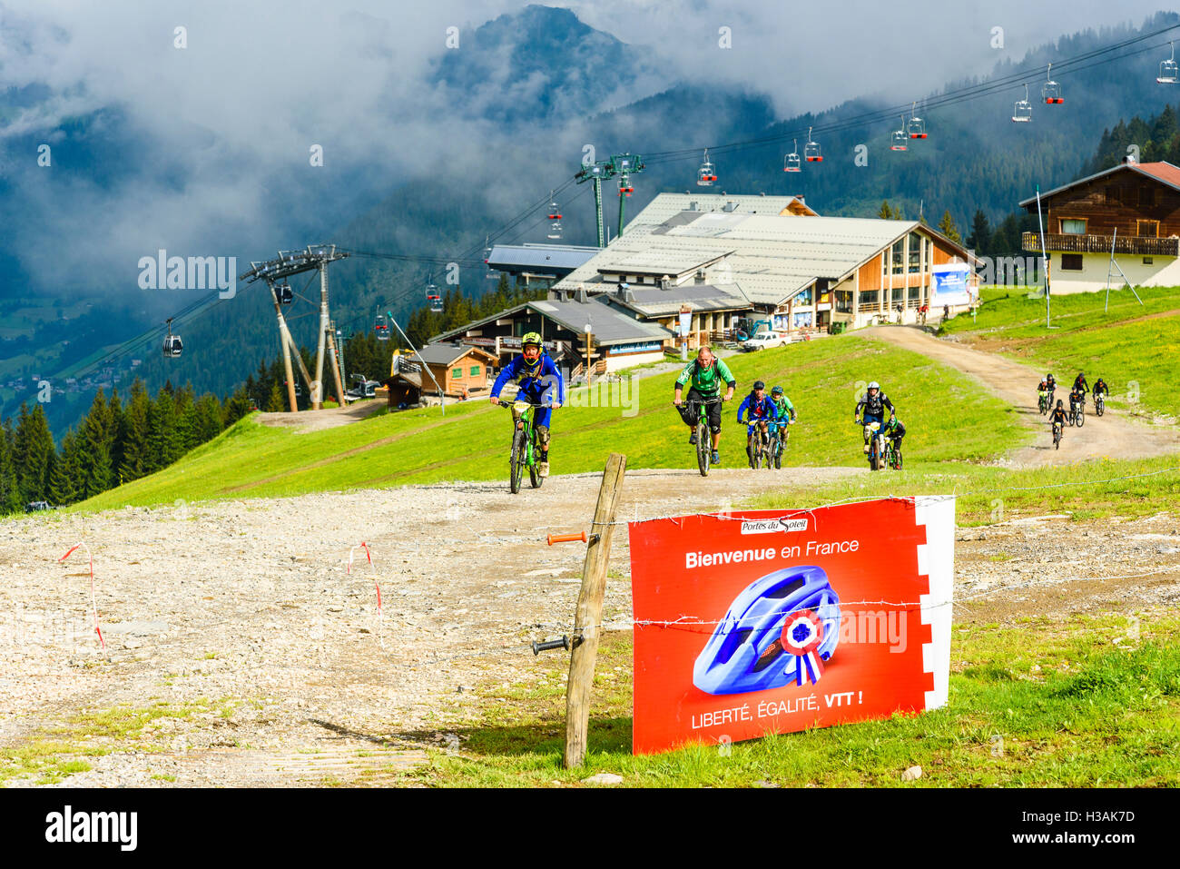 Riders approaching the French-Swiss border during Pass'Portes du Soleil MTB 2016 mountain bike event - Stock Image