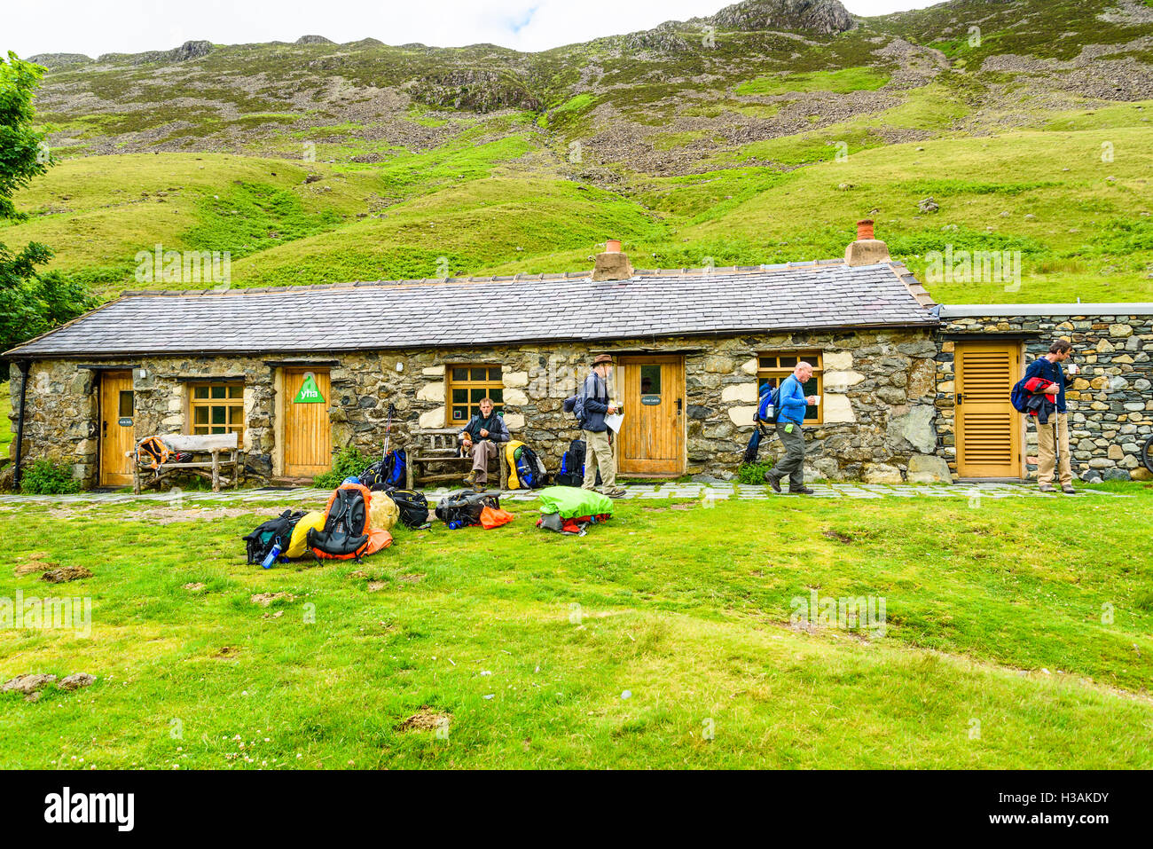 Walkers outside Black Sail hut, a remote youth hostel at the head of Ennerdale in the Lake District Cumbria - Stock Image