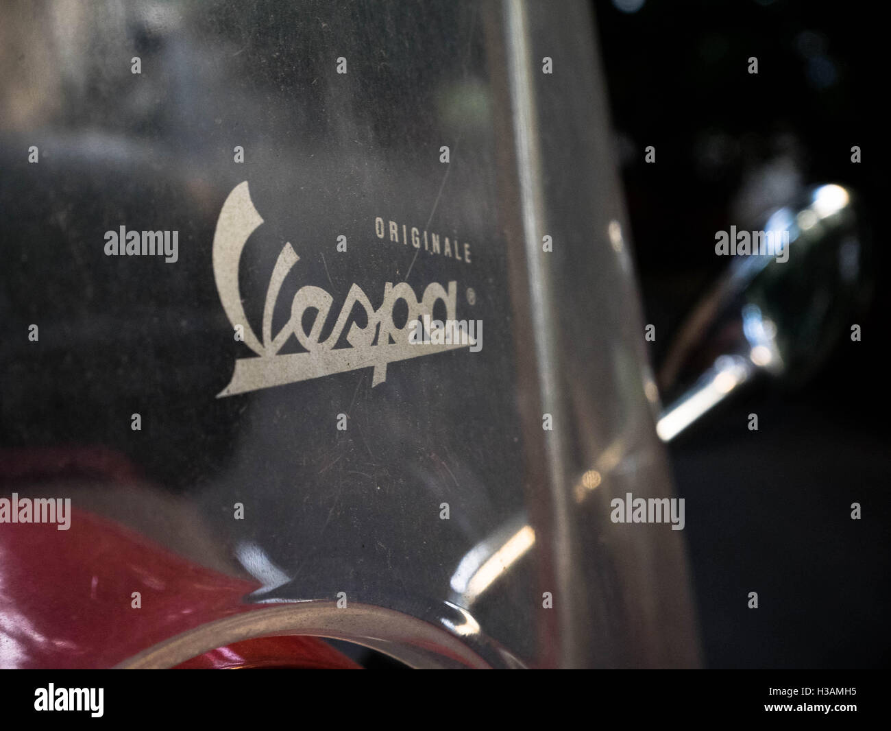 Vespa logo sticker glued on fron protective wind shield on a scooter. - Stock Image