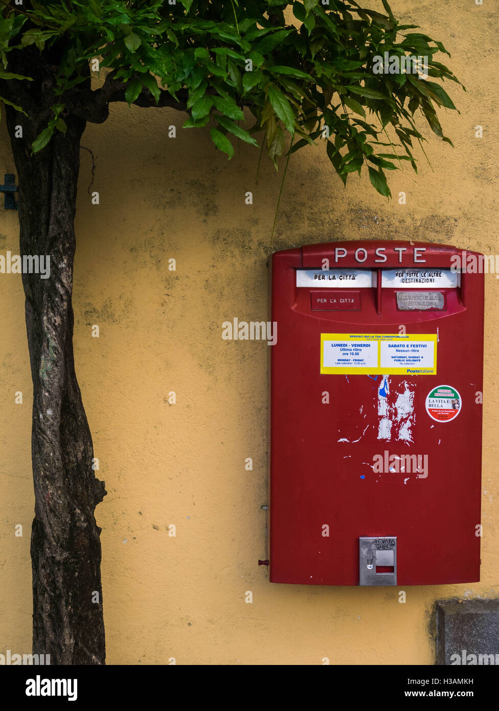 Mail box for post in Italy, red on yellow wall. - Stock Image