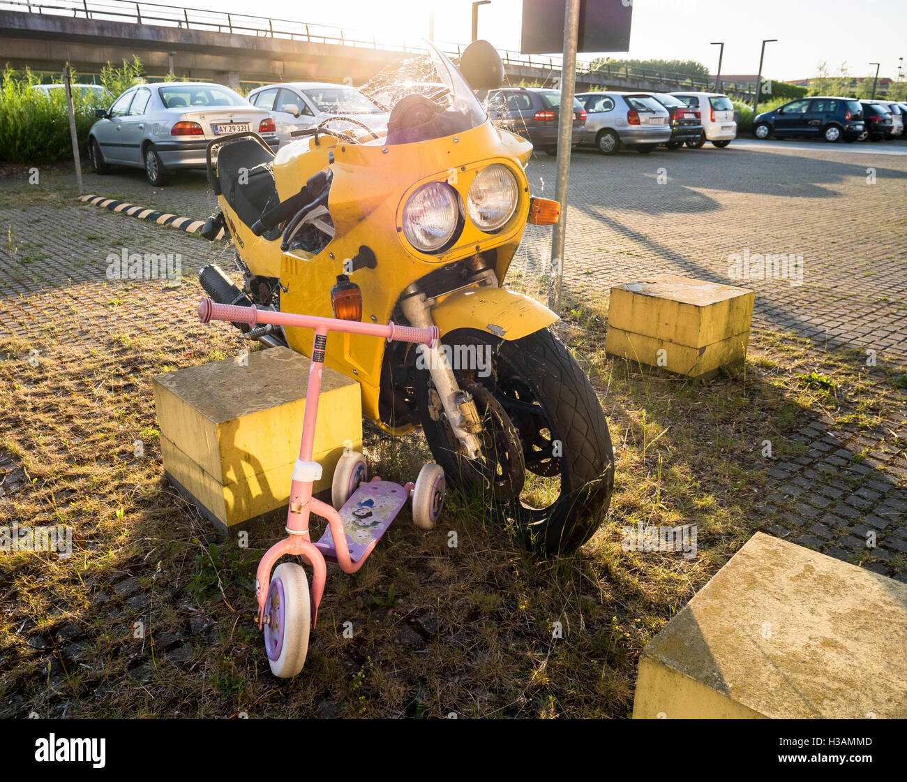 Yellow motorcycle left standing abandoned in a parking lot together with a small kids scooter - Stock Image