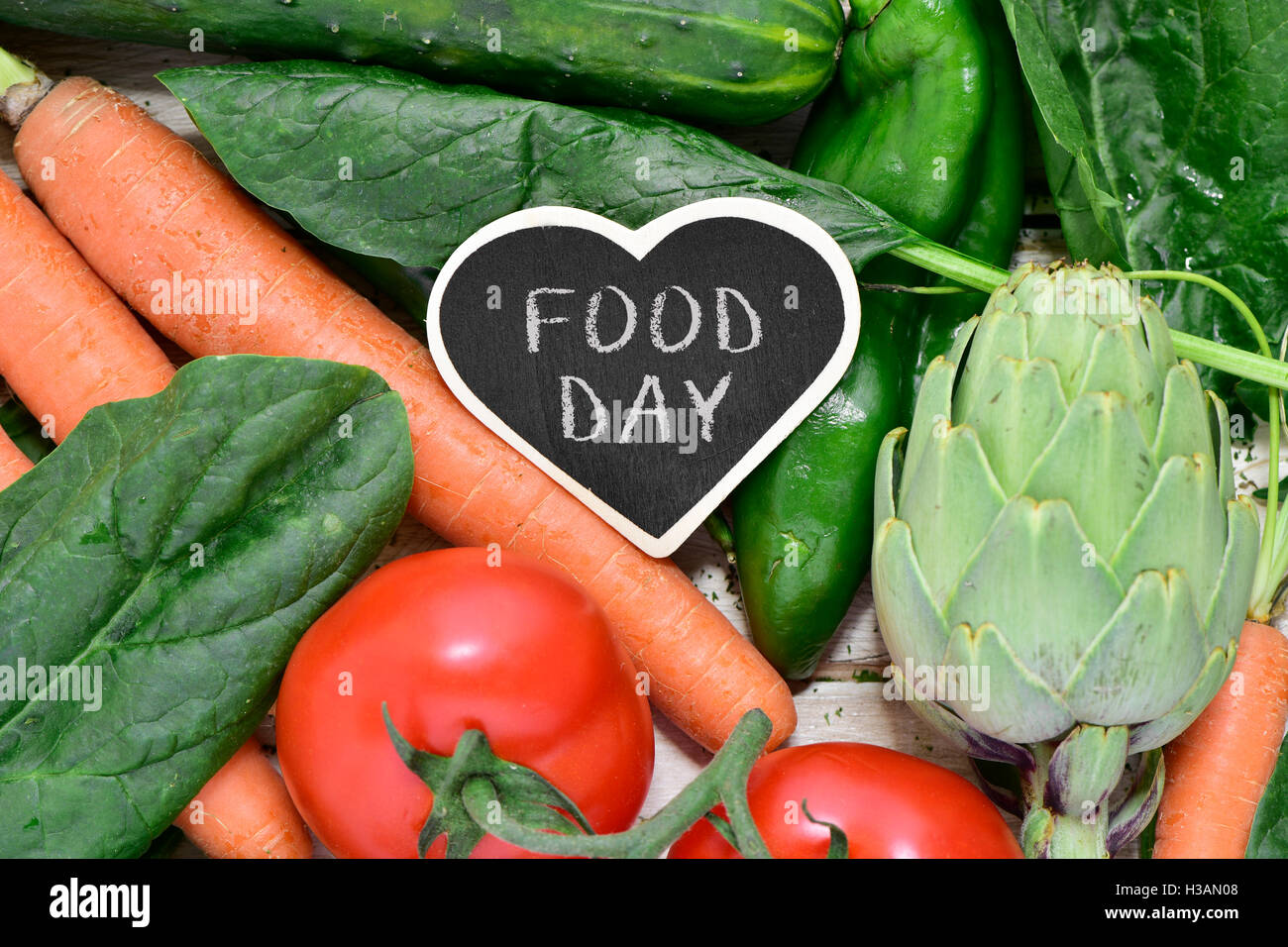 closeup of a heat-shaped chalkboard with the text food day placed on a pile of some different raw vegetables, such - Stock Image