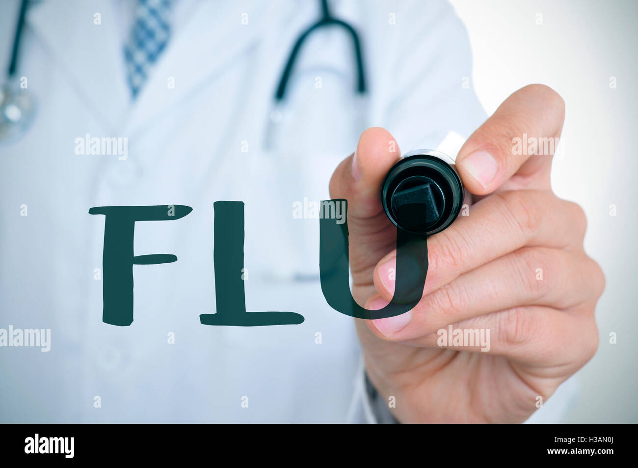 closeup of a young caucasian doctor man writing the word flu in the foreground with a black marker pen - Stock Image