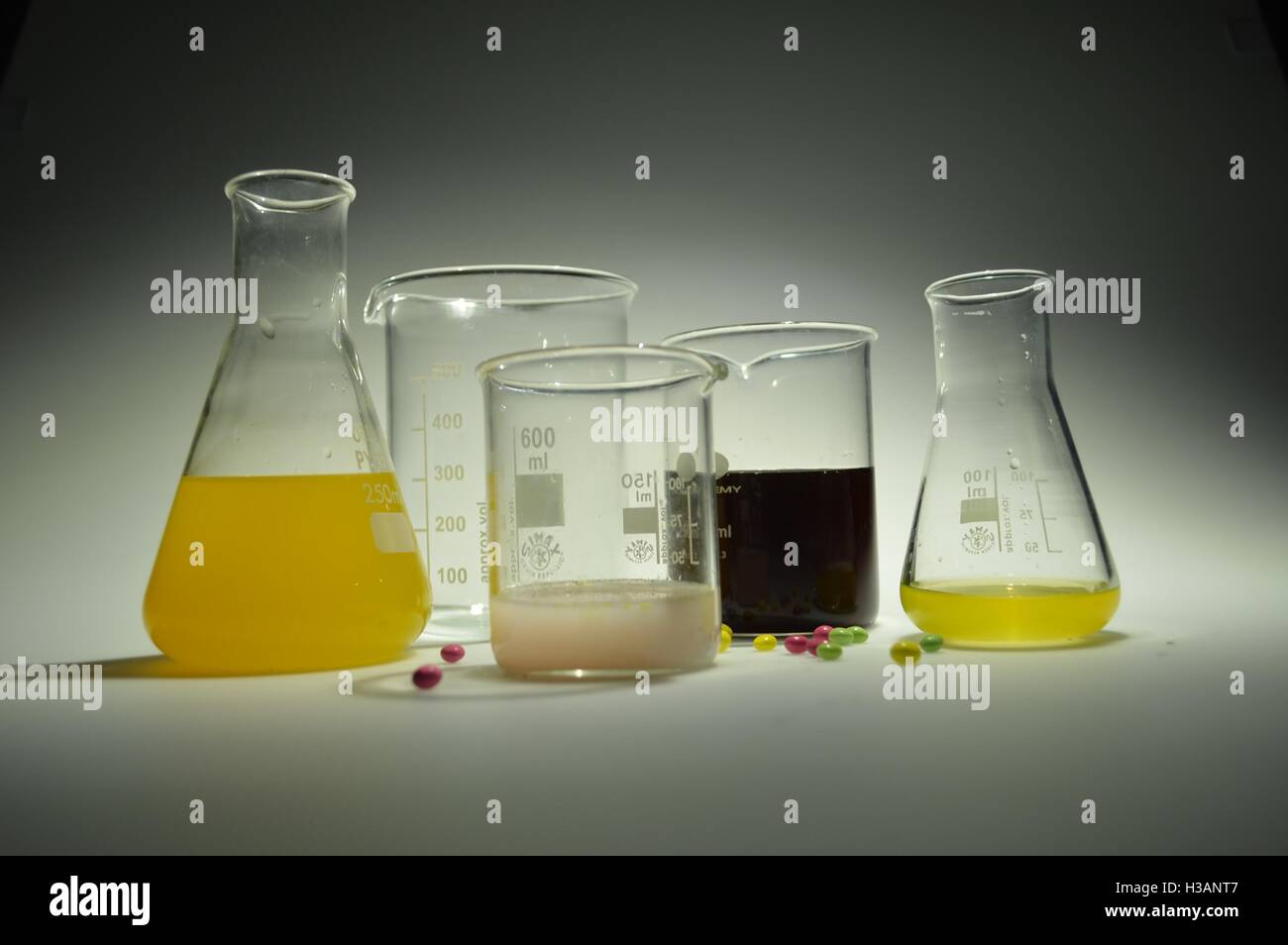 Science lab with colourful liquid chemicals in beakers, flasks and jugs. Stock Photo