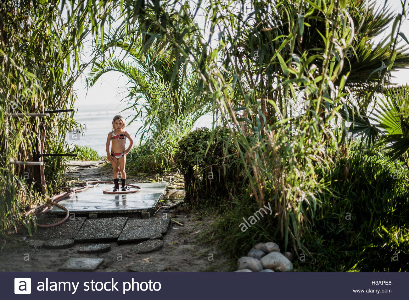 little girl rinsing off after playing in the ocean - Stock Image