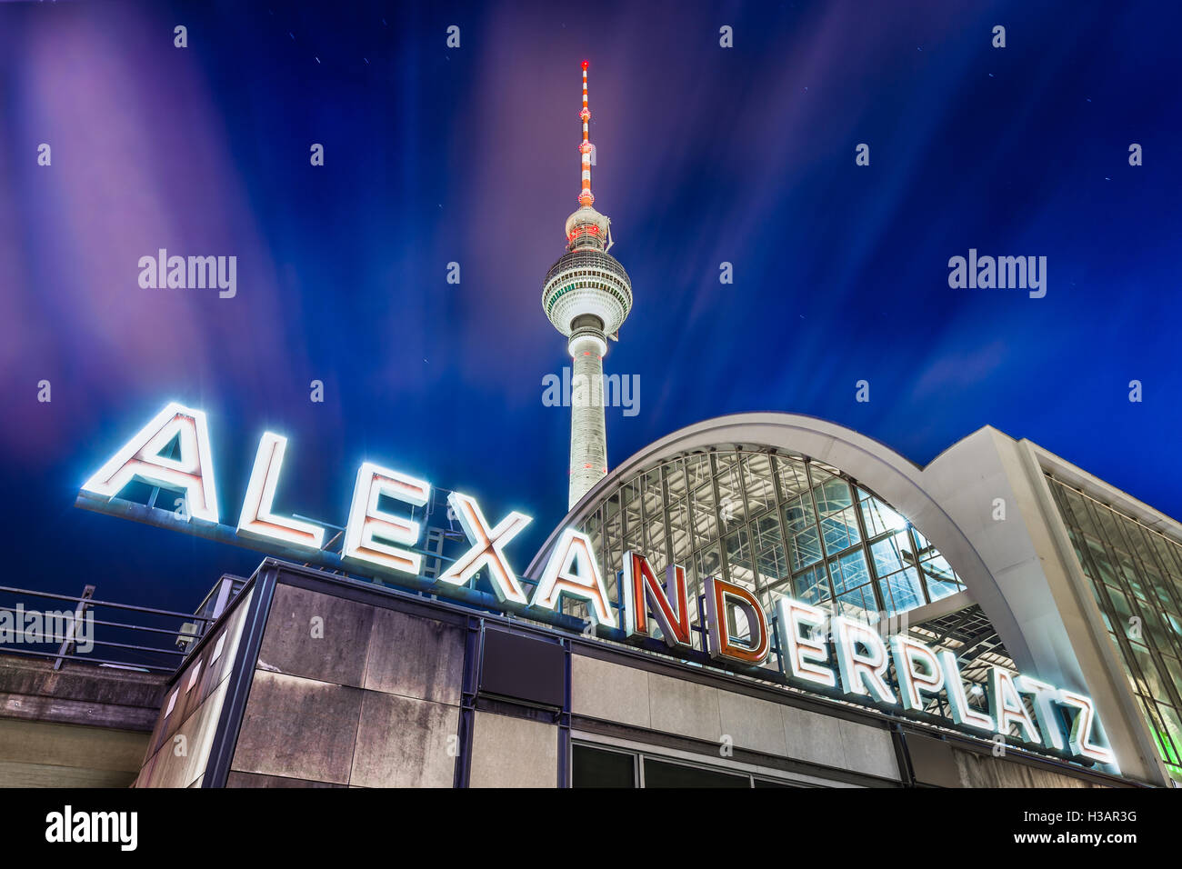 Classic wide-angle view of Alexanderplatz neon sign with famous TV tower and train station at night Berlin, Germany - Stock Image