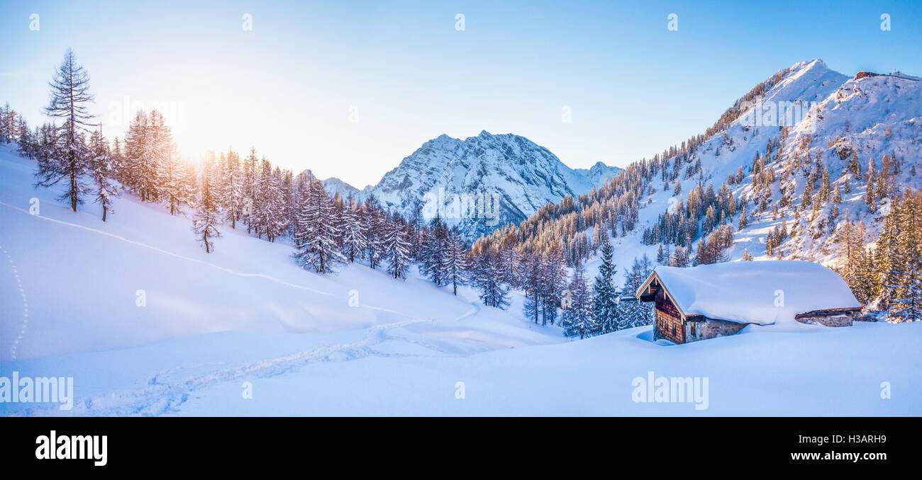 Panoramic view of beautiful winter wonderland mountain scenery with traditional mountain cabin the background in - Stock Image