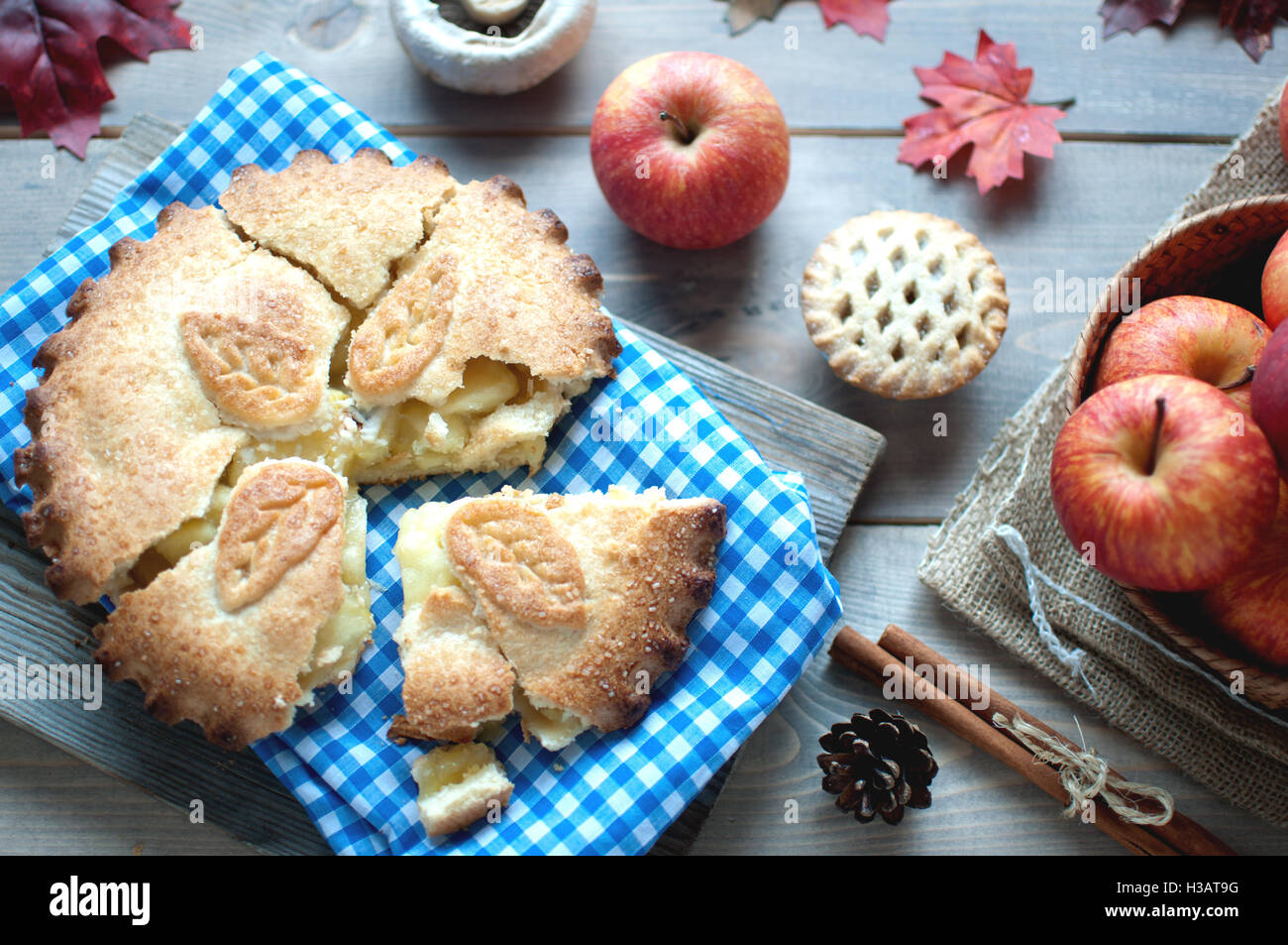 Sliced apple pie with fruit ingredients and cinammon sticks on one side - Stock Image