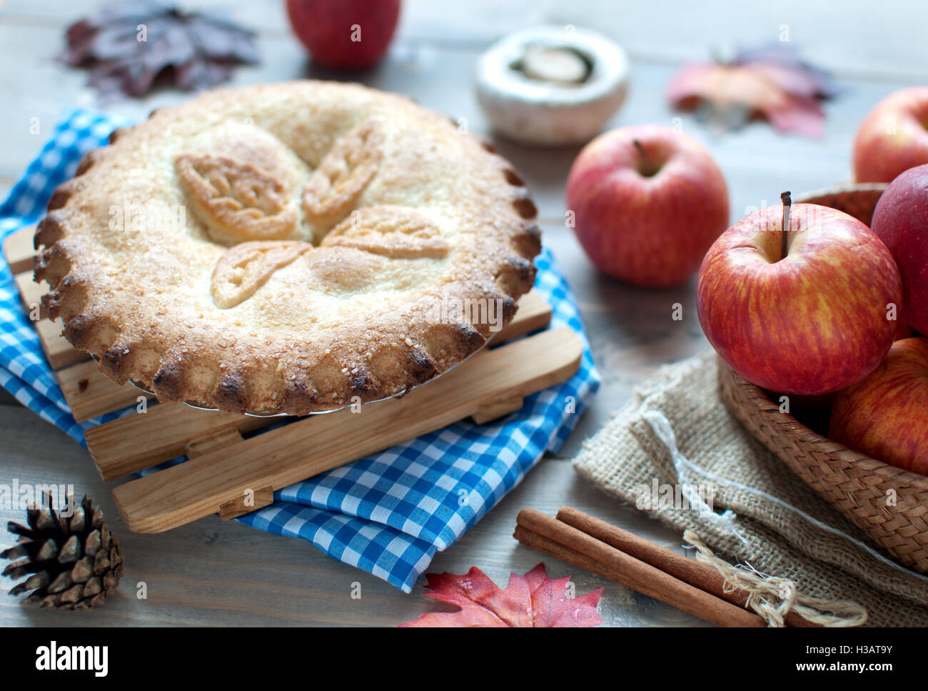Apple pie with fruit ingredients autumn leaves and cinammon sticks on a wooden table - Stock Image