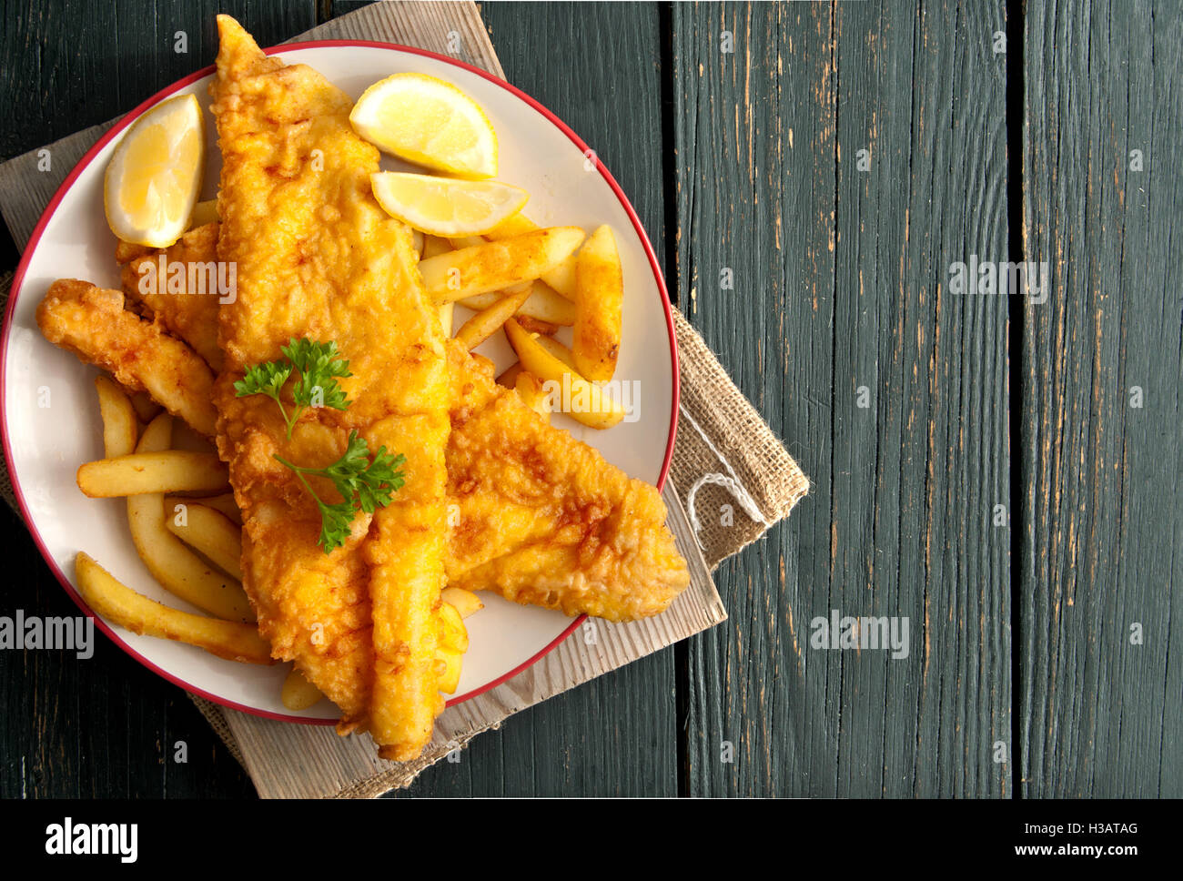 Close up of battered fish on a plate with chips - Stock Image