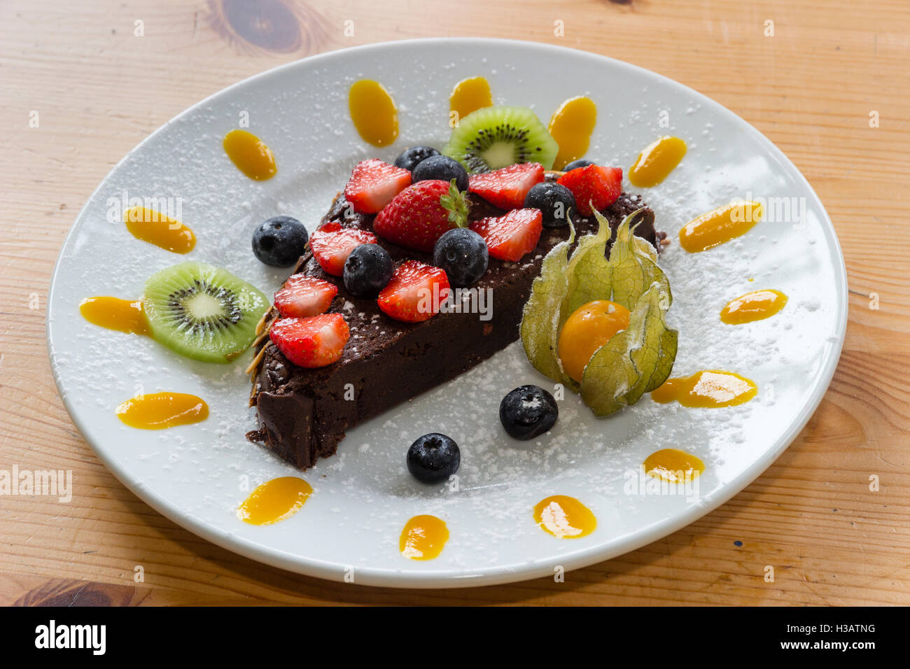 'Death by Garden House' rich chocolate cake decorated with fruit and fruit puree - Stock Image