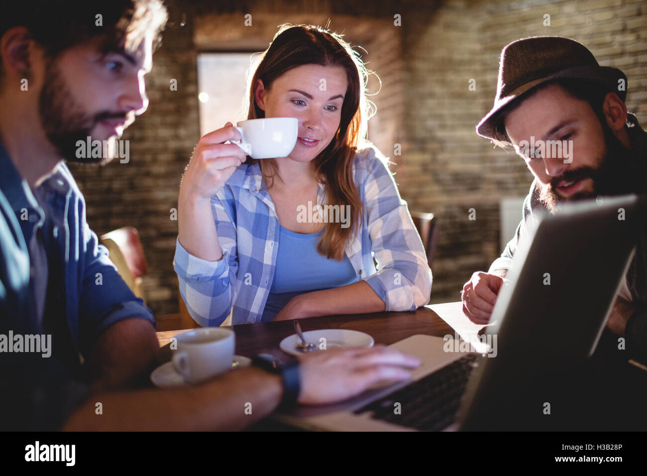 Young customers using laptop at cafe - Stock Image