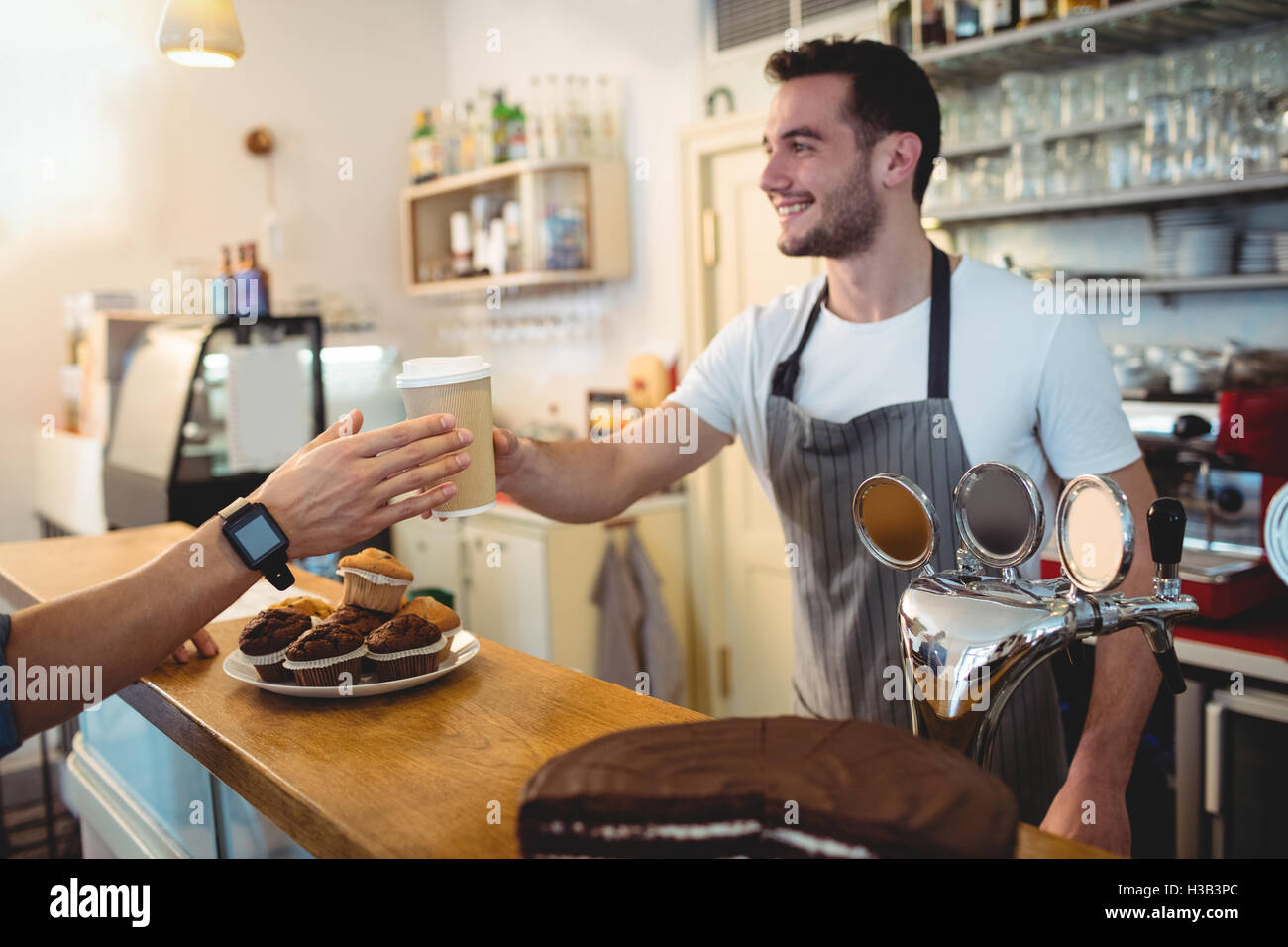 Happy barista serving coffee to customer at cafe - Stock Image