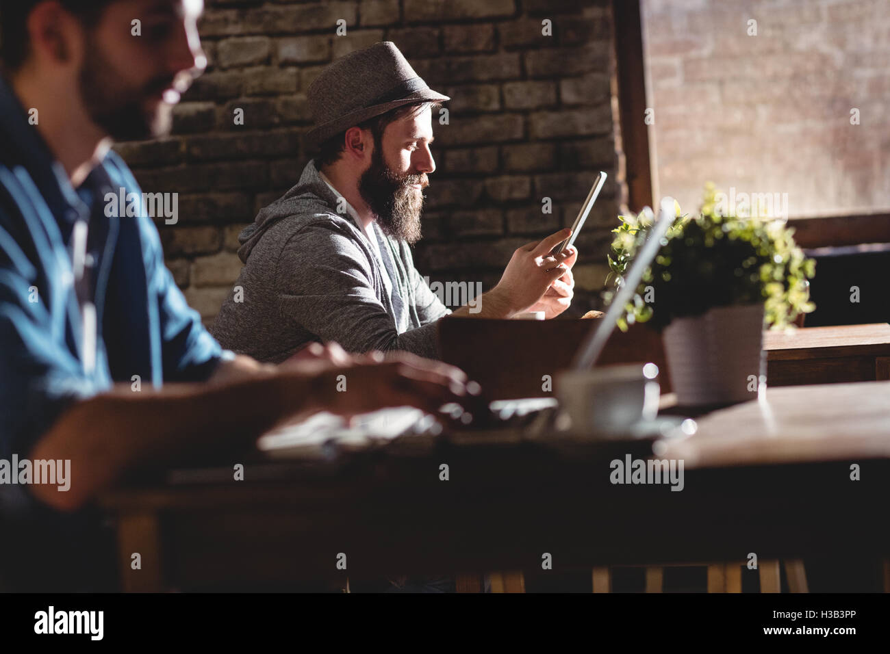 Side view of customers using technologies at cafe - Stock Image