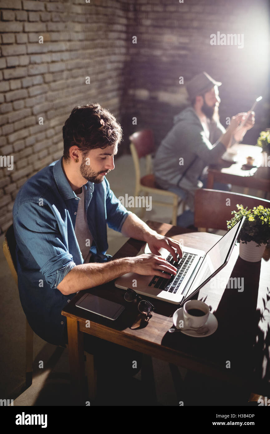 Handsome man working on laptop at cafe - Stock Image