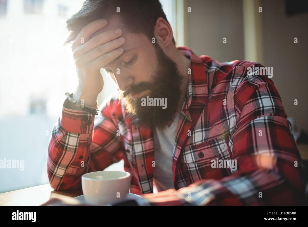 Unhappy customer sitting at cafe - Stock Image