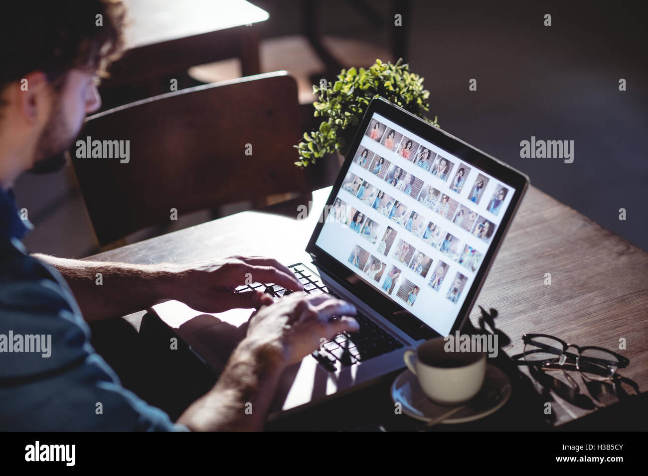 High angle view of man working on laptop at cafe - Stock Image
