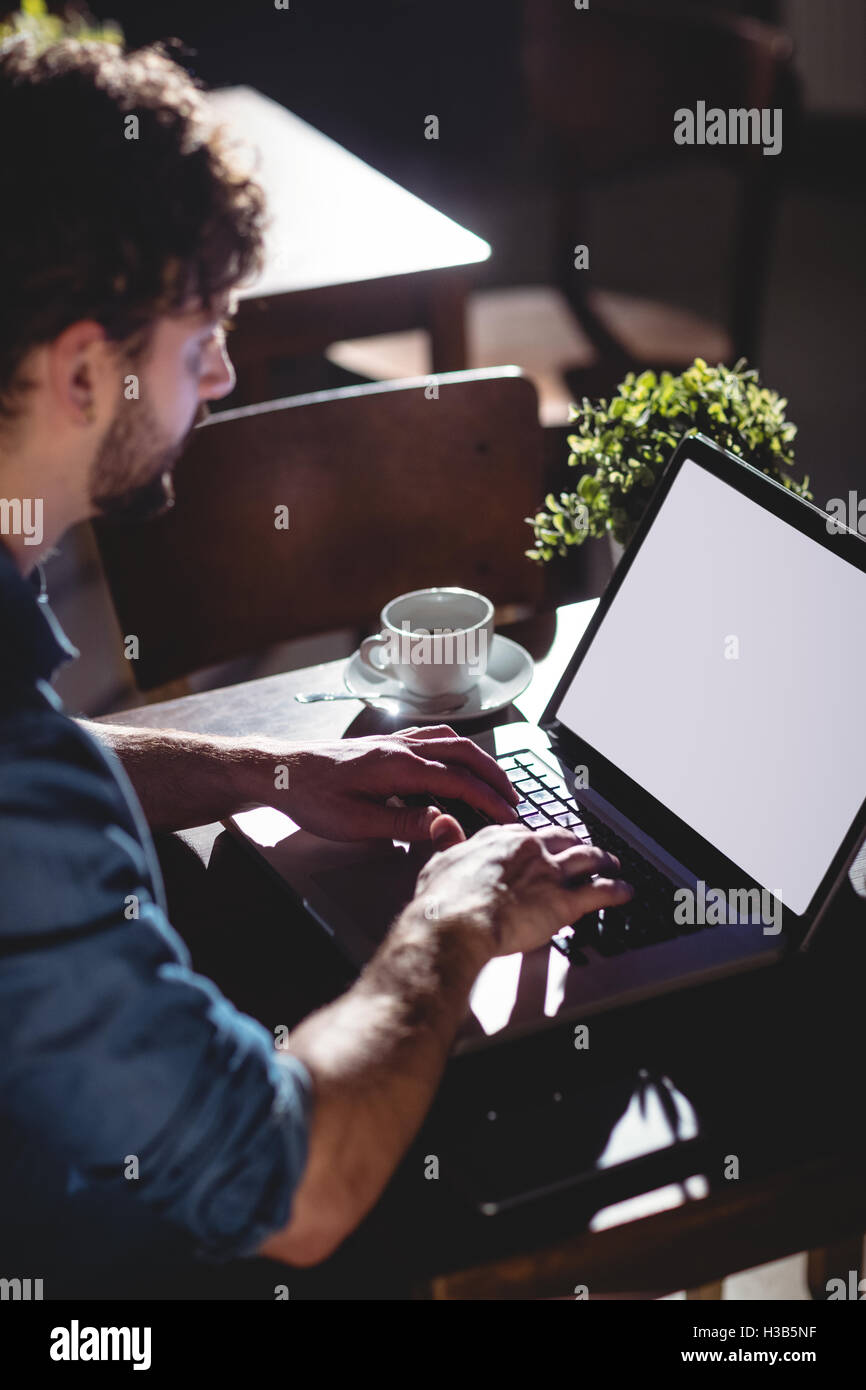 High angle view of customer typing on laptop at cafe - Stock Image
