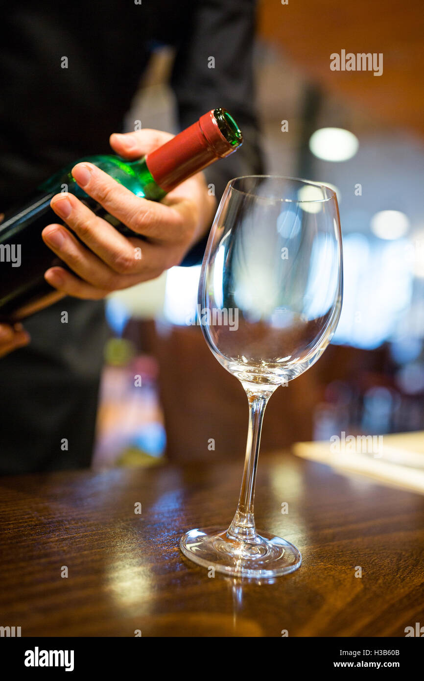 Waiter pouring red wine into glass - Stock Image