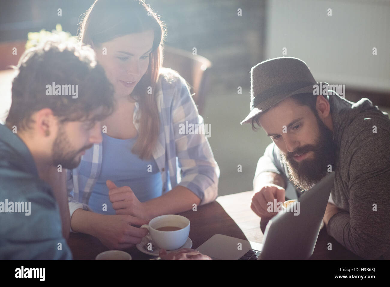Young customers looking at laptop at cafe - Stock Image