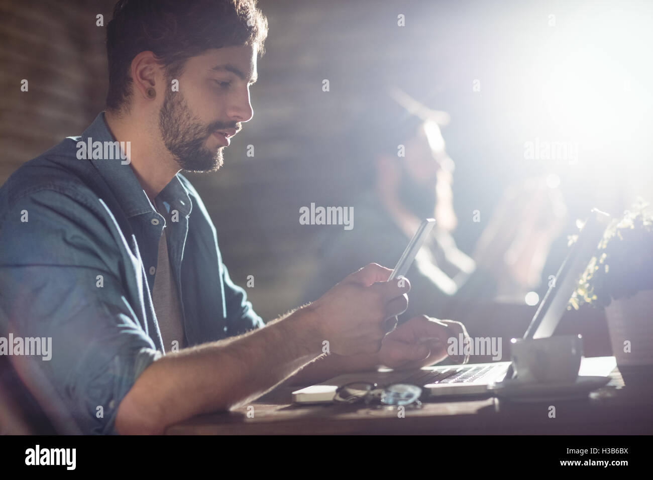 Side view of handsome man using cellphone at cafe - Stock Image