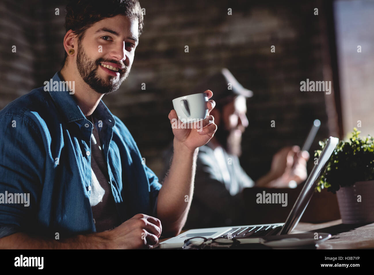 Portrait of happy man with coffee at cafe - Stock Image