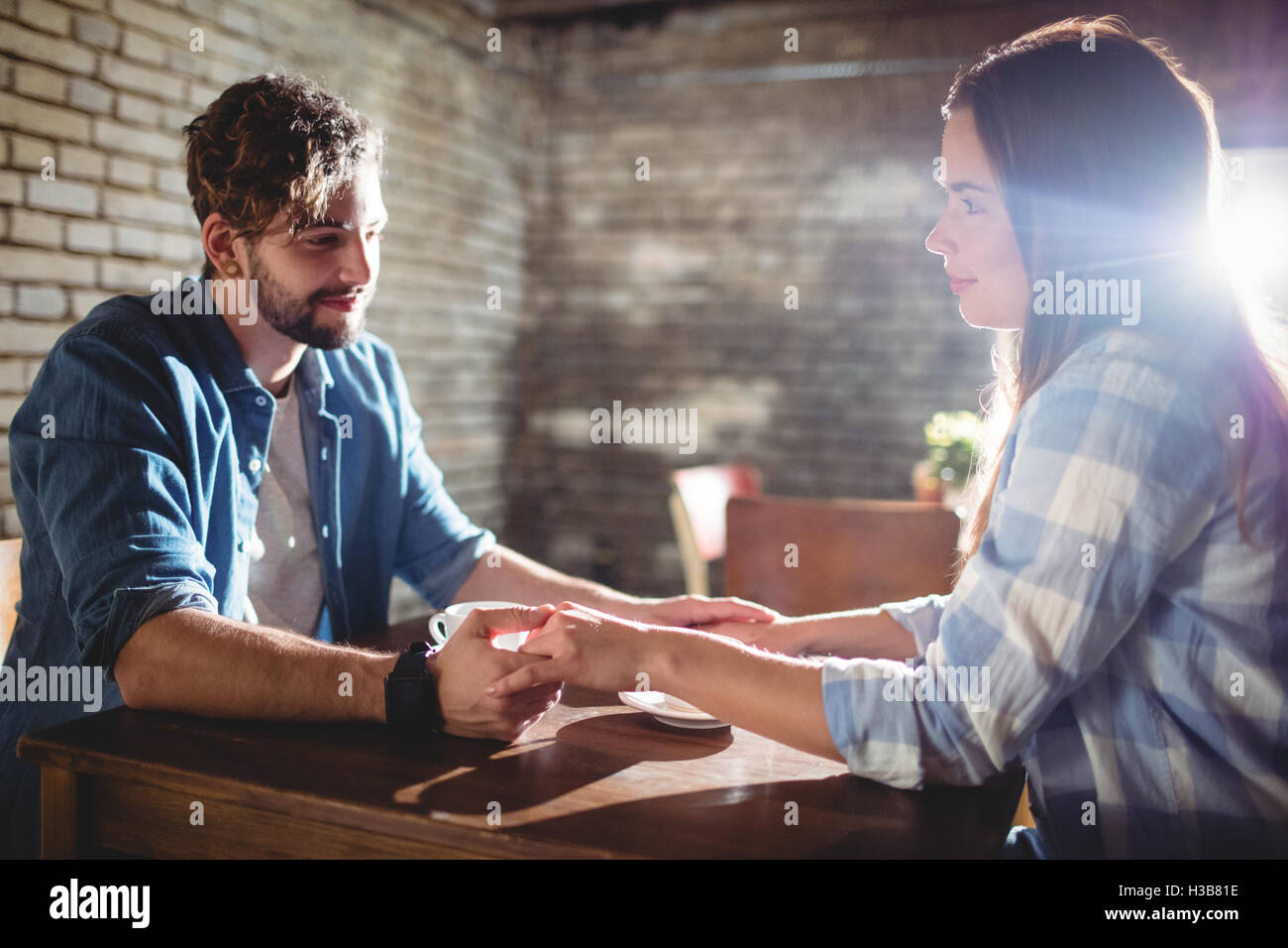 Happy couple holding hands at cafe - Stock Image