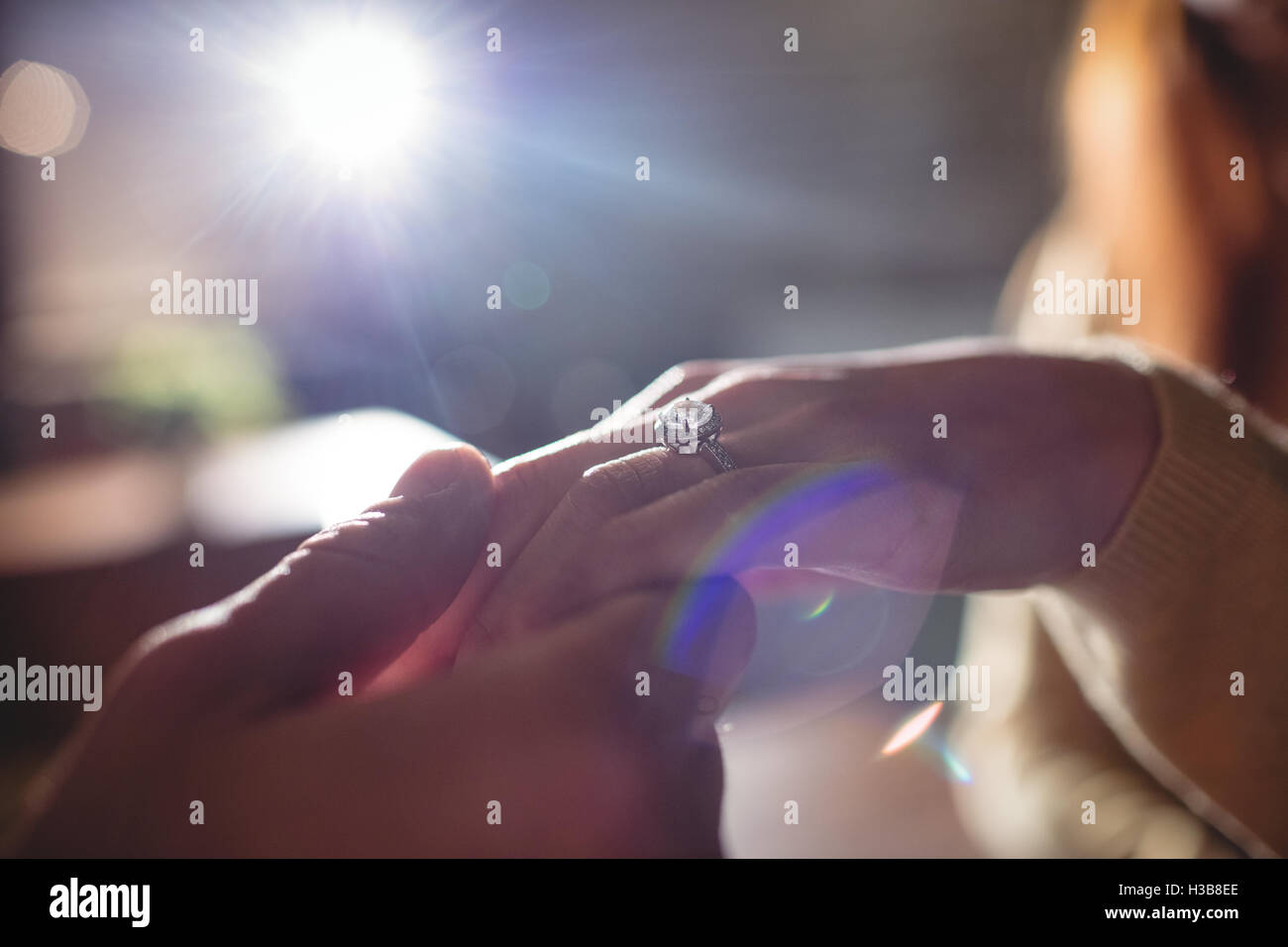 Close-up of couple holding hands with engagement ring at cafe - Stock Image