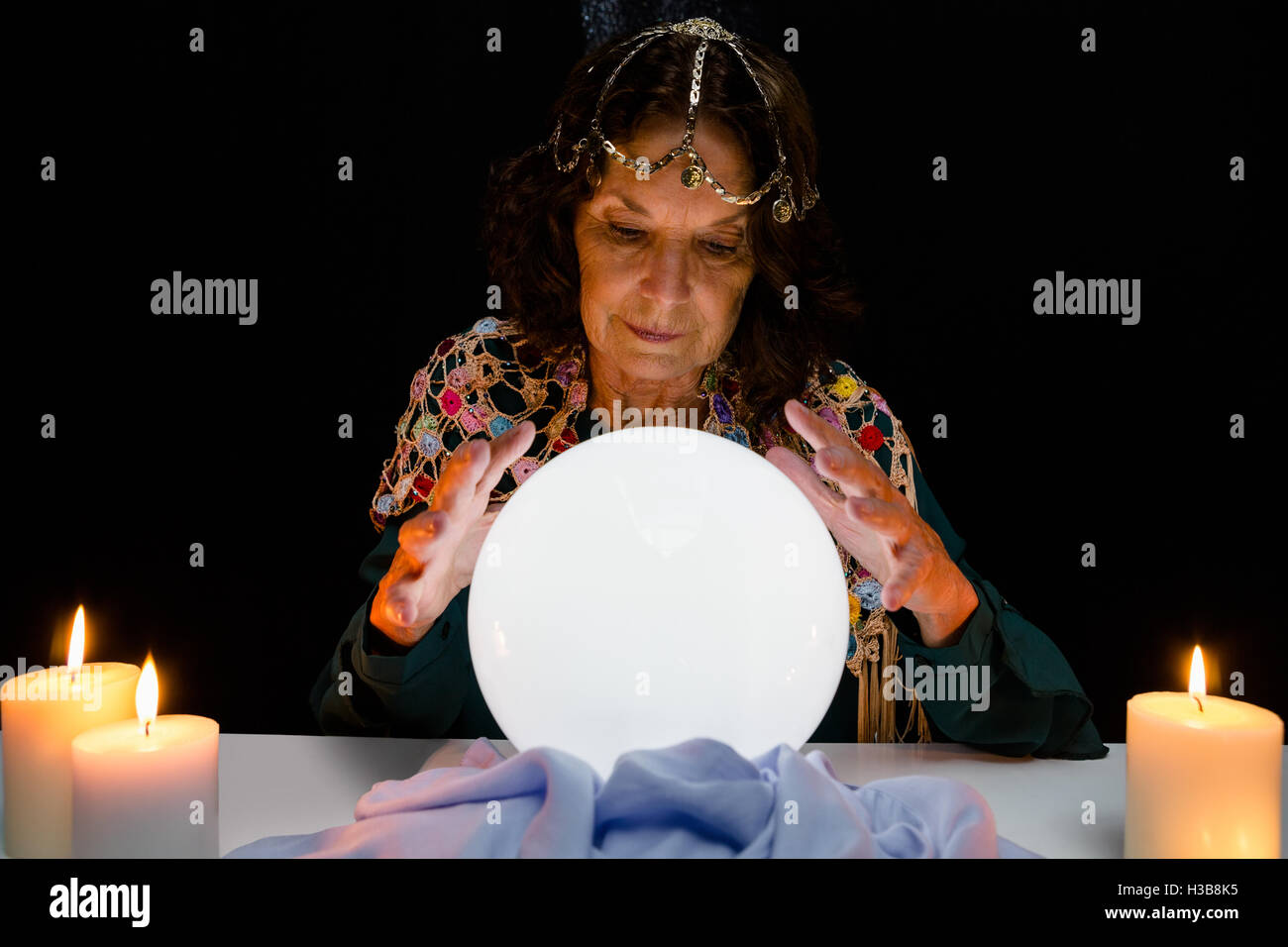 Mature fortune teller with crystal ball while forecasting - Stock Image