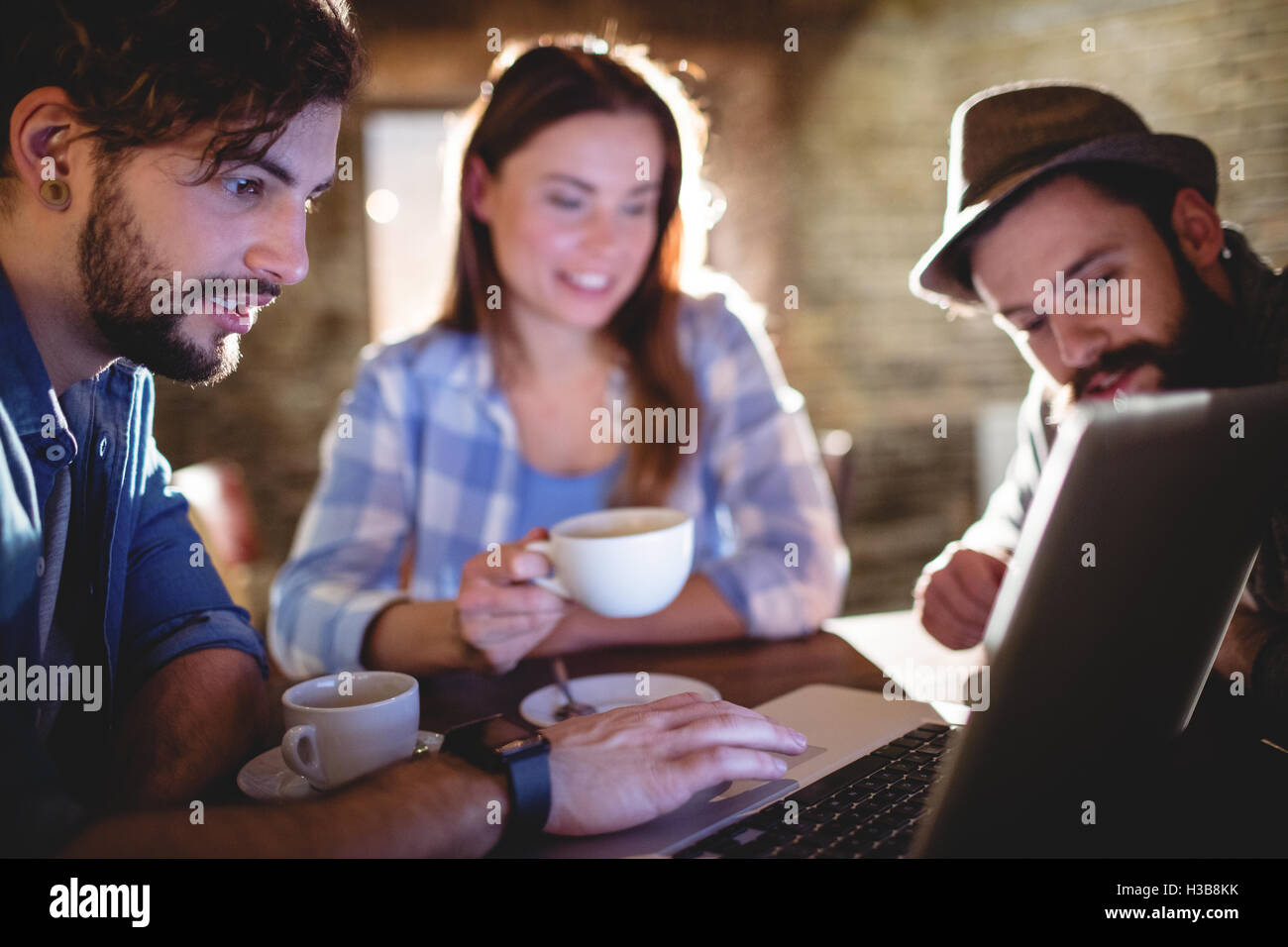 Man showing laptop to friends at cafe - Stock Image