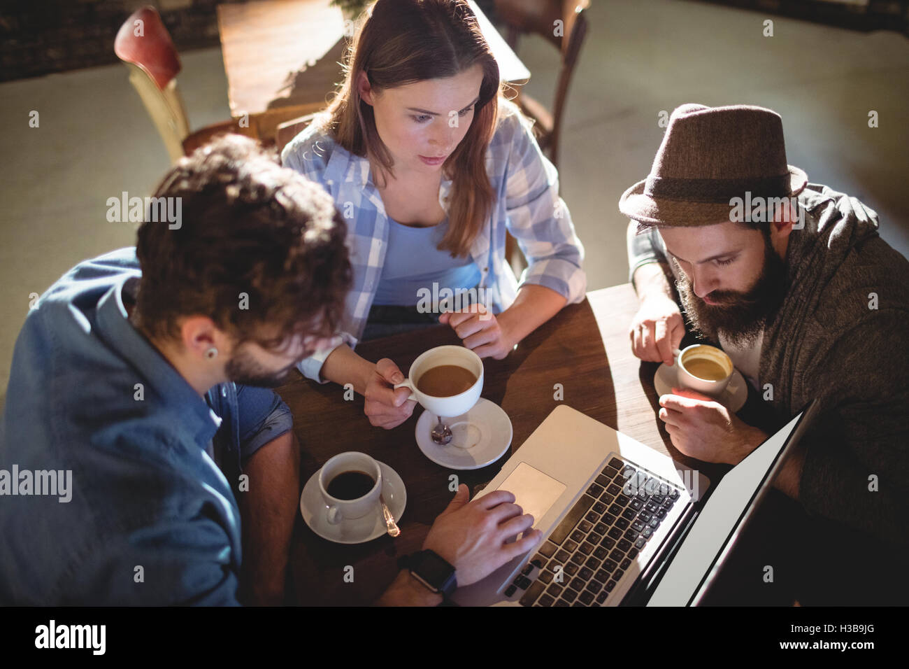 High angle view of friends using laptop at cafe - Stock Image