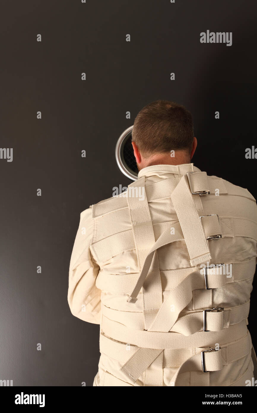 Photo of a insane man in his forties wearing a straitjacket looking out the hole of an asylum door. - Stock Image