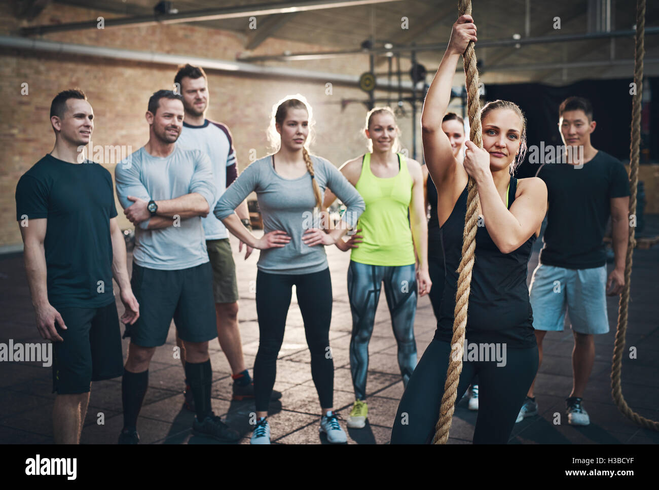 Group of adults watching woman use climbing rope in fitness exercise circuit training regimen - Stock Image