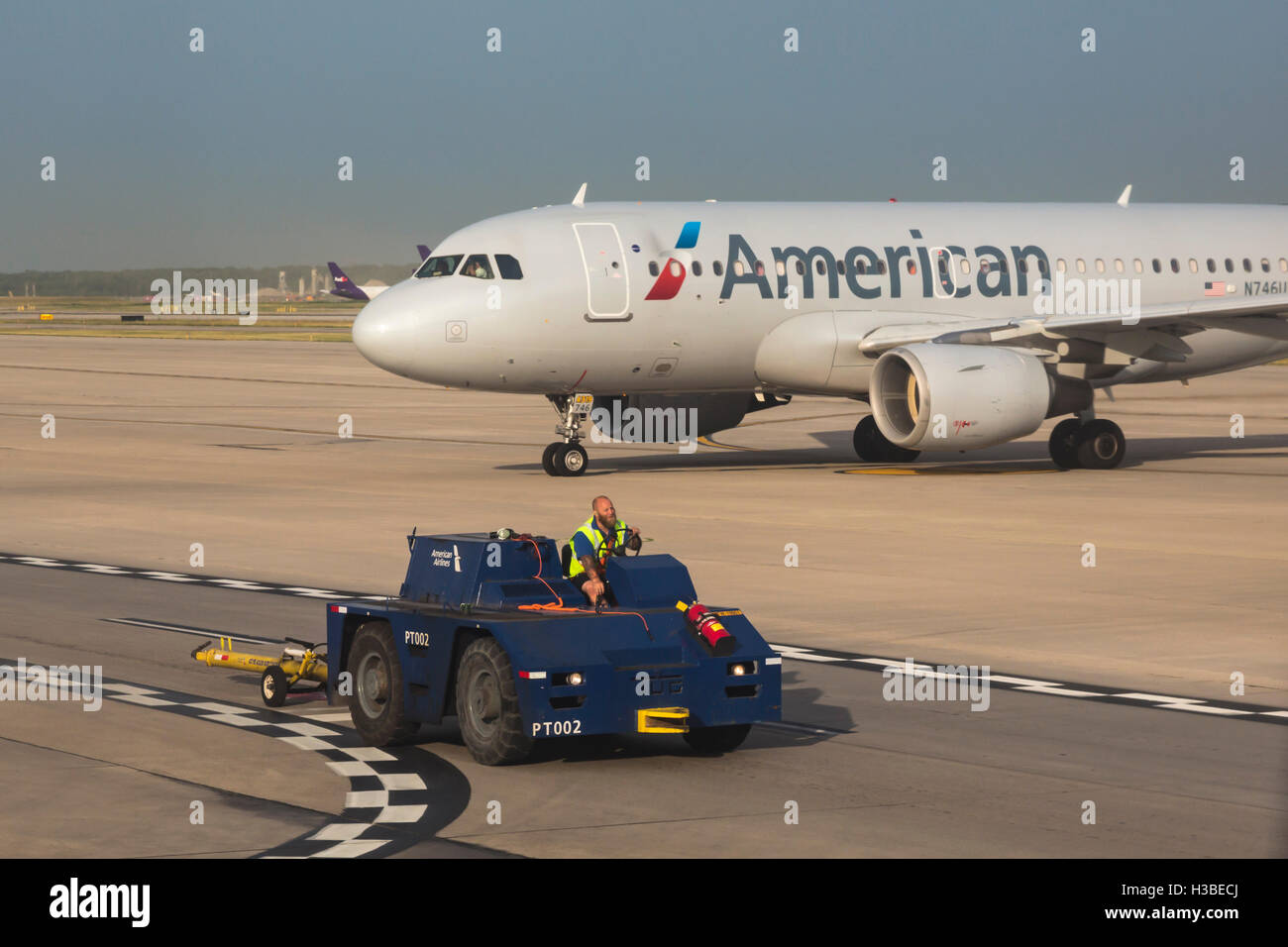 Detroit Michigan A Worker Drives A Tug Past An American Airlines Stock Photo Alamy