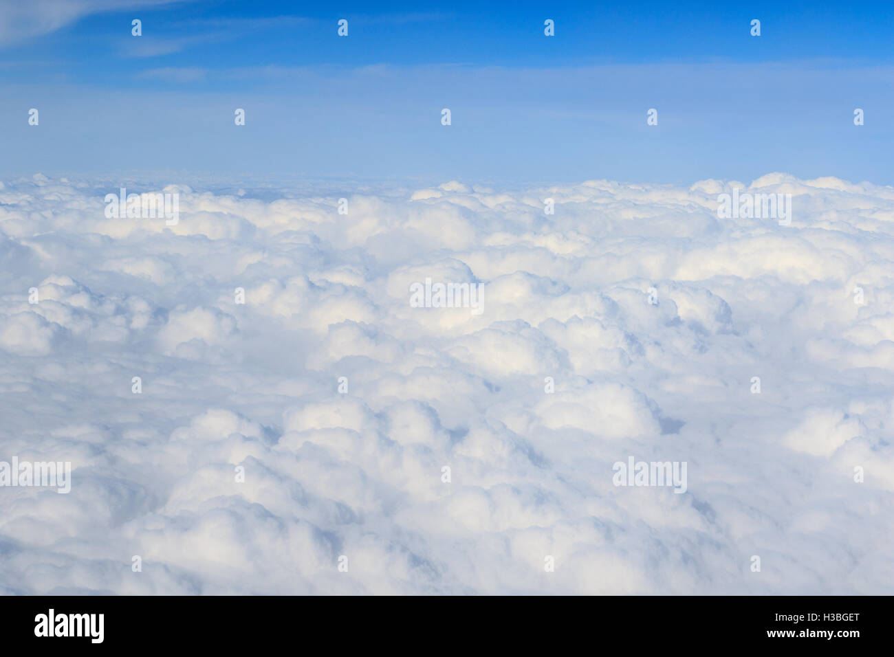 white fluffy clouds high up from a plane - Stock Image