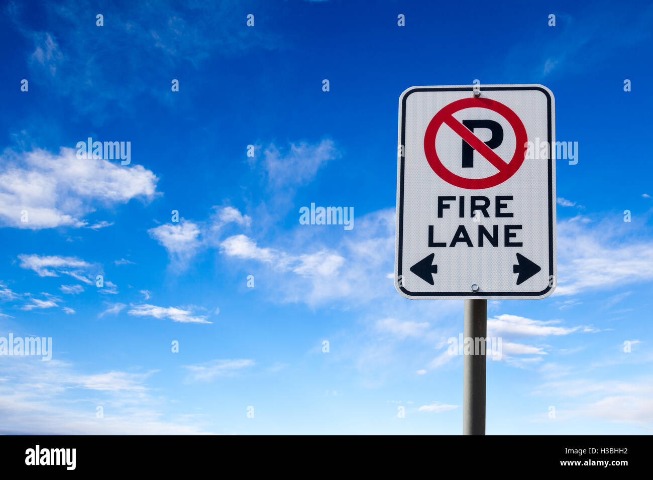 A Fire Lane No Parking sign against a blue cloudy sky with copy space. Horizontal orientation. - Stock Image