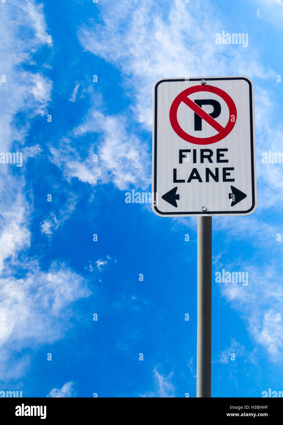A Fire Lane No Parking sign against a blue cloudy sky with copy space. Vertical orientation.Stock Photo