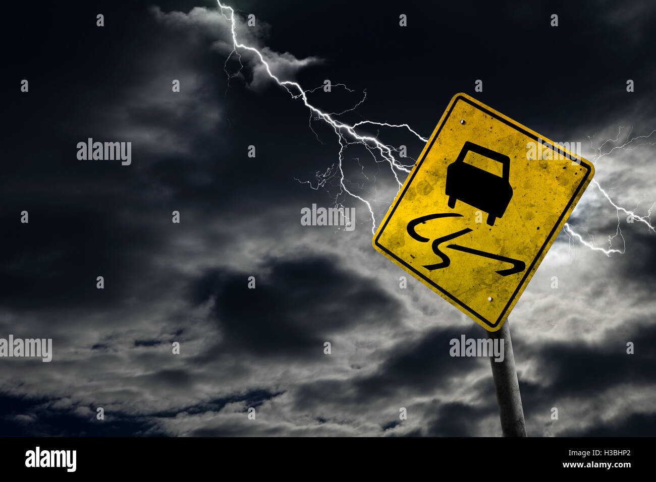 Slippery when wet road sign against a stormy background with lightning and copy space. Dirty and angled sign adds - Stock Image