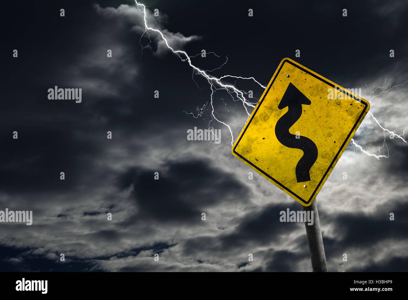 Winding road sign against a stormy background with lightning and copy space. Dirty and angled sign adds to the drama. - Stock Image