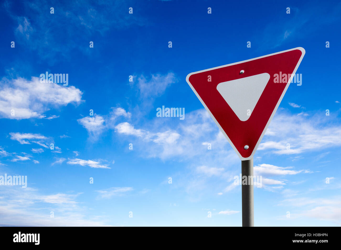 Conceptual yield sign against a blue cloudy sky. - Stock Image