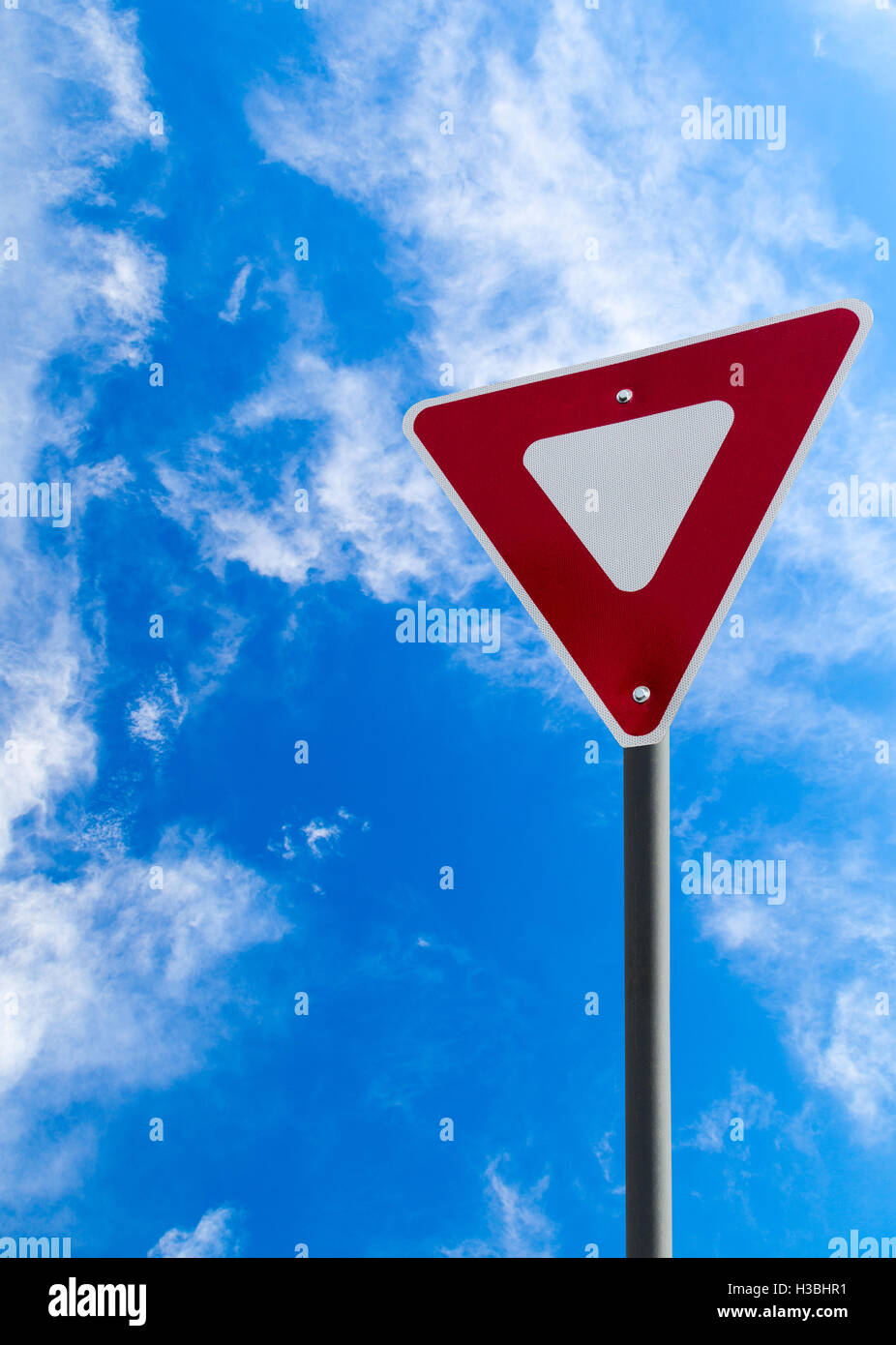 Traffic yield sign against a blue cloudy sky with copy space. Vertical orientation. - Stock Image