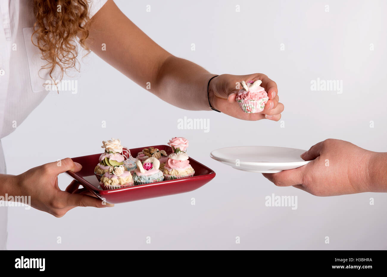 A waitress serving a tray of fairy cakes - Stock Image