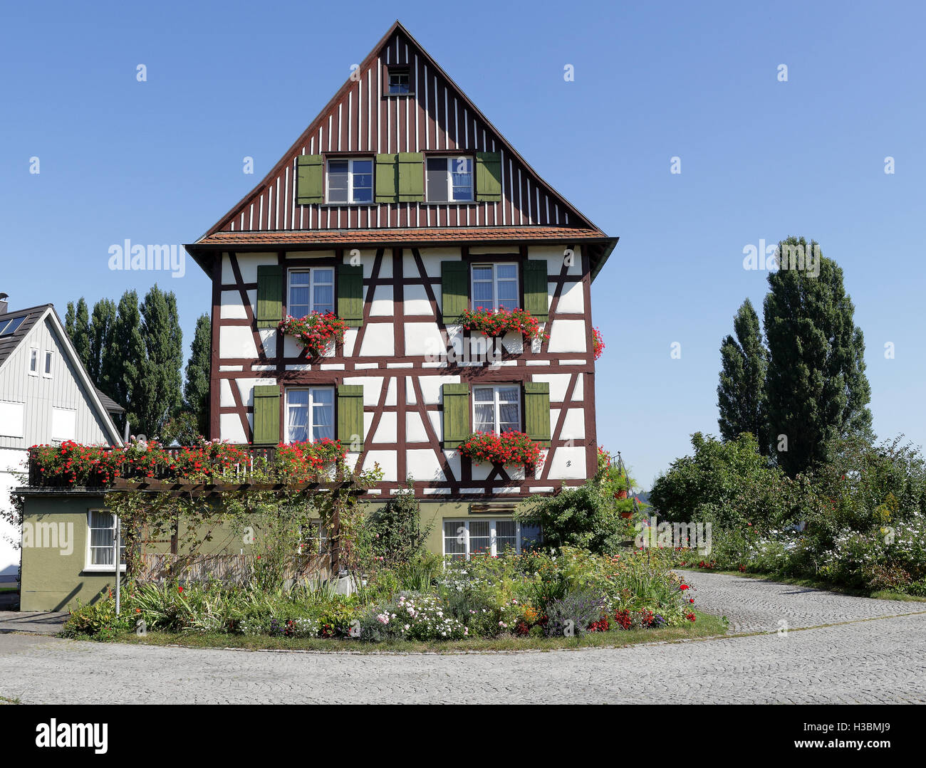 Traditional timber framed German village house with shutters and window boxes - Stock Image