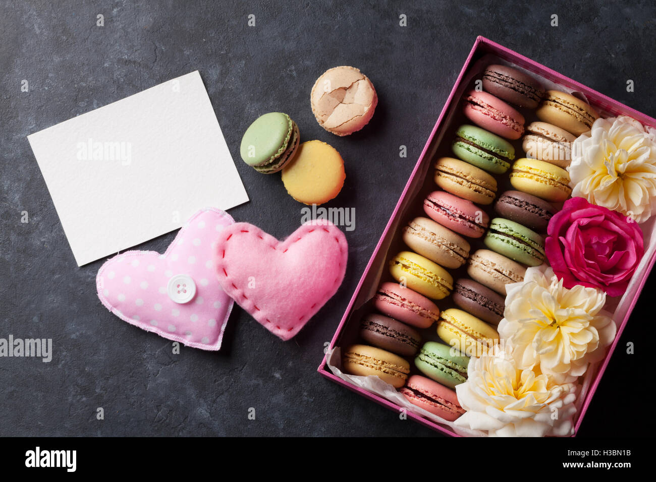 Colorful macaroons and greeting card. Sweet macarons in gift box and hearts. Top view with copy space for your text - Stock Image
