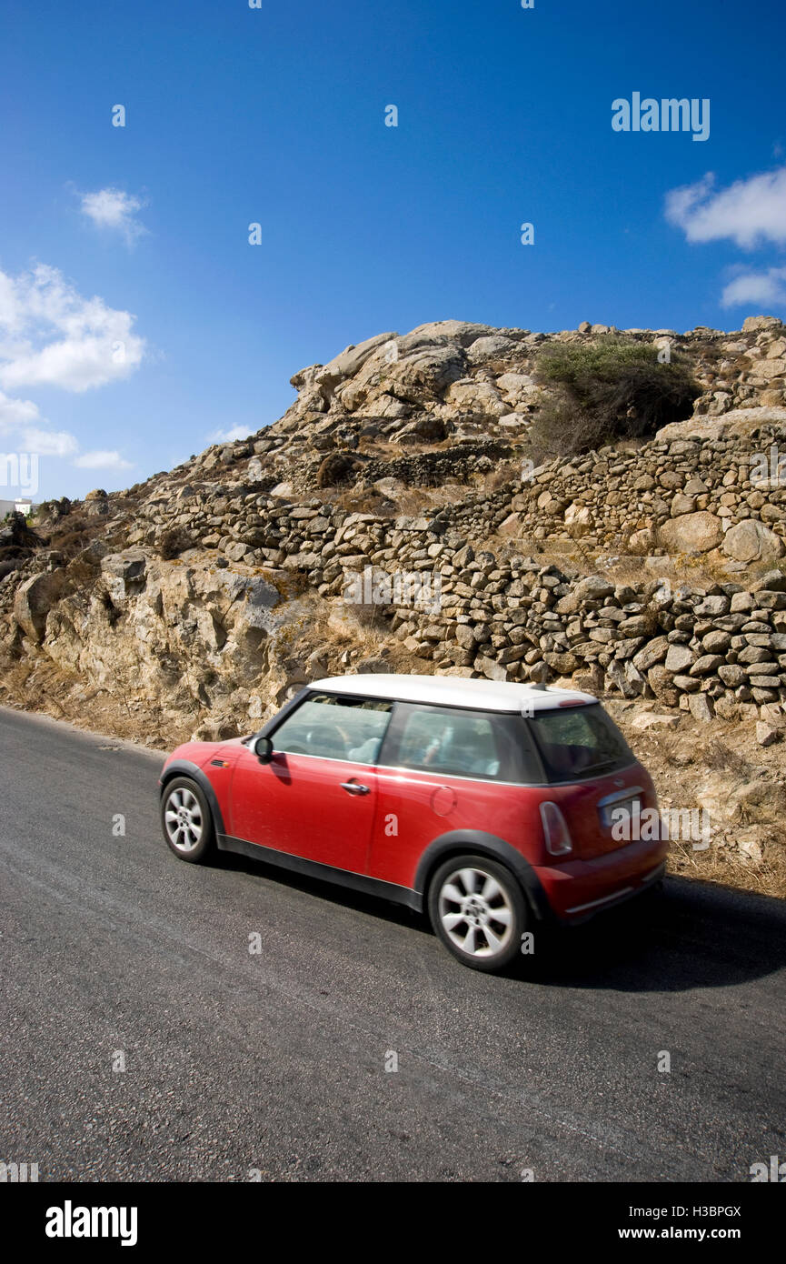 Mini Cooper car driving on road on Mykonos Island in Greece - Stock Image