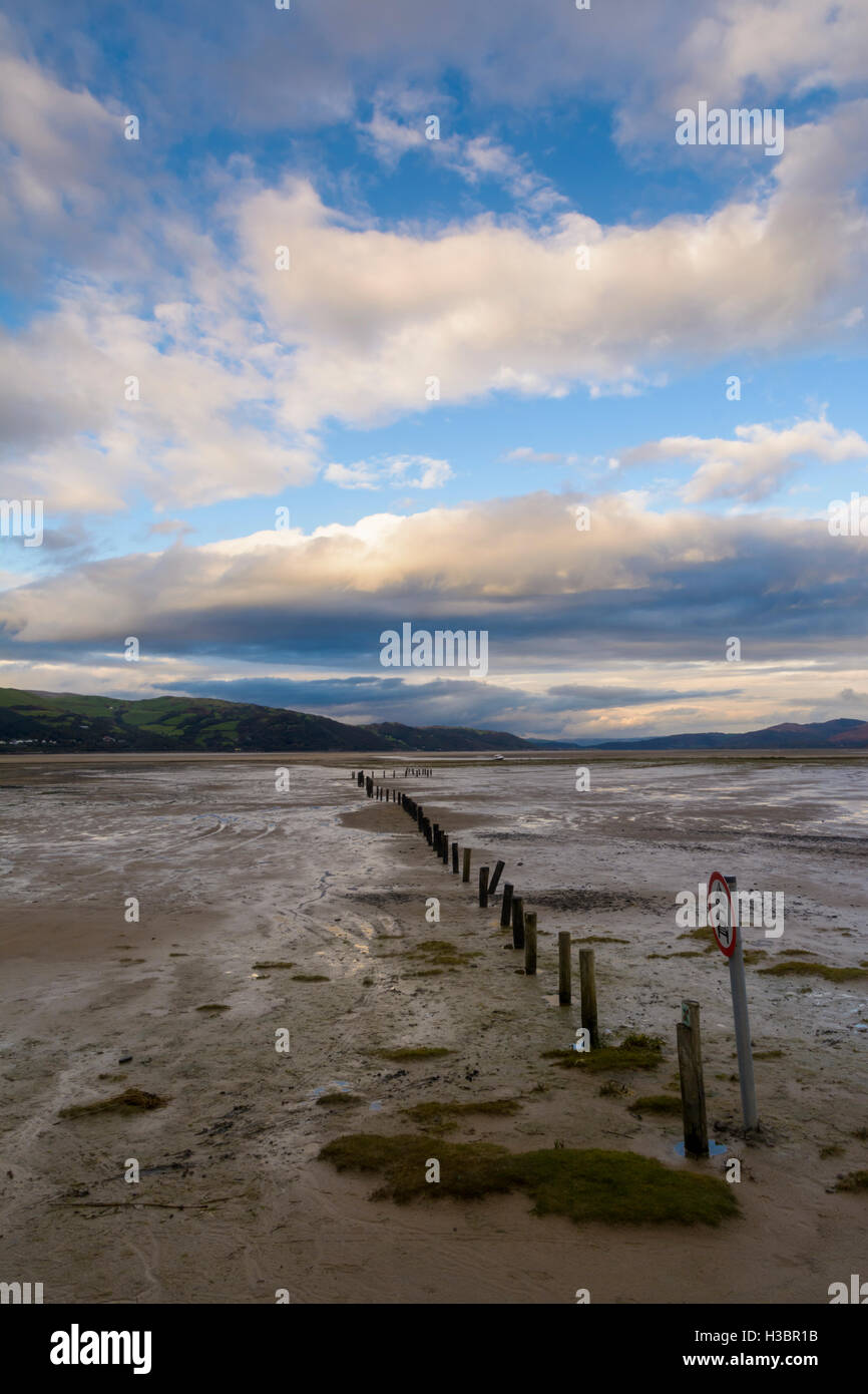 A row of posts leading towards the horizon at dusk in then Dyfi estuary, Wales, UK Stock Photo