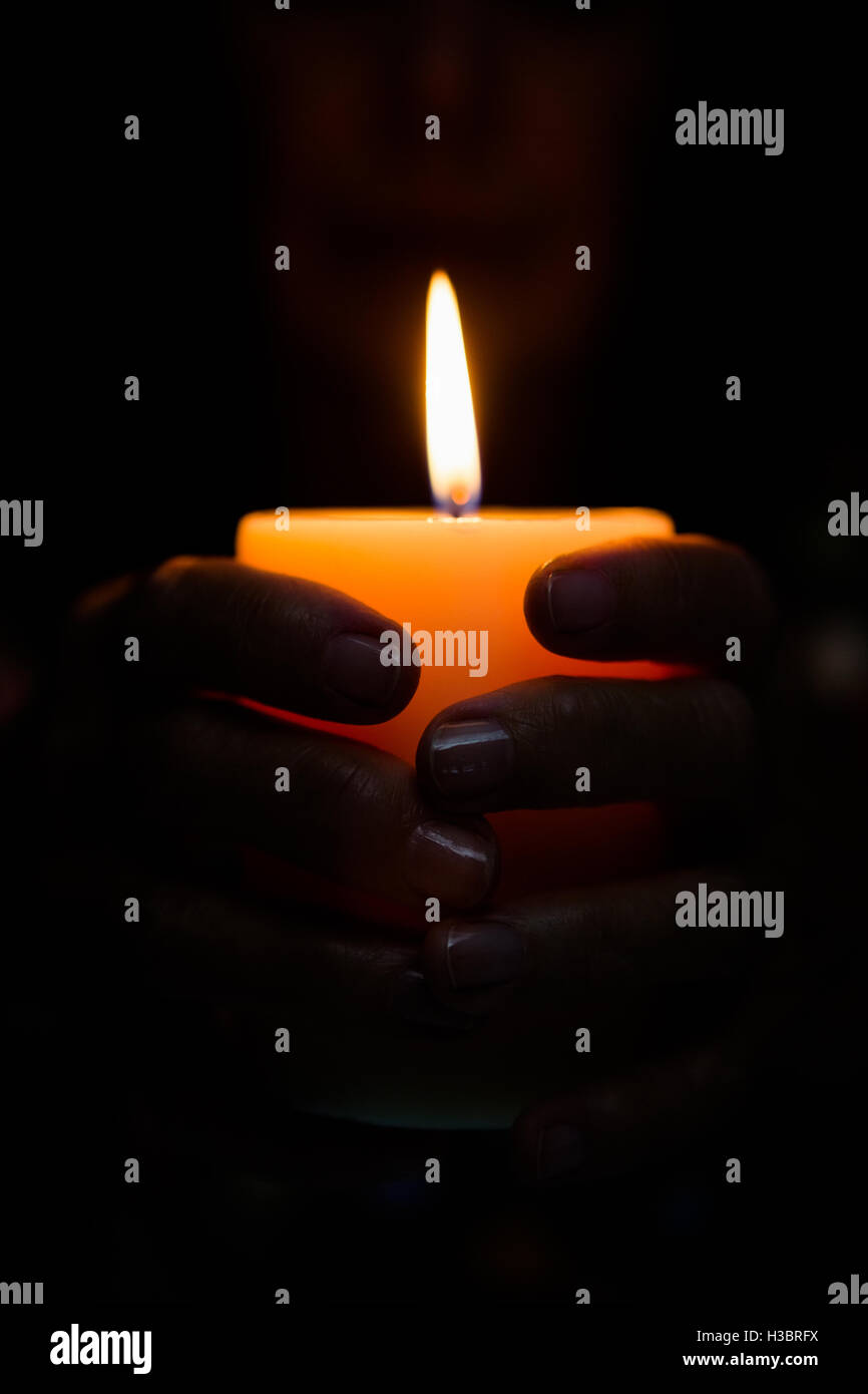 Cropped image of fortune teller holding lit candle - Stock Image